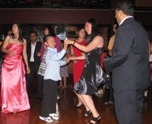 Asian Boy Dancing with Friends and Family