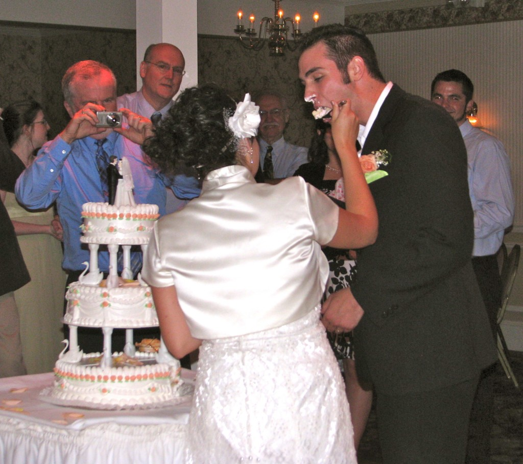 Bride and Groom Cake Cutting with Friends and Family Dancing with Fun Wedding DJ